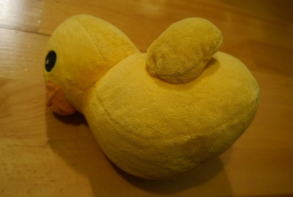 A photo of a cuddly toy yellow duck which has fallen over onto its side